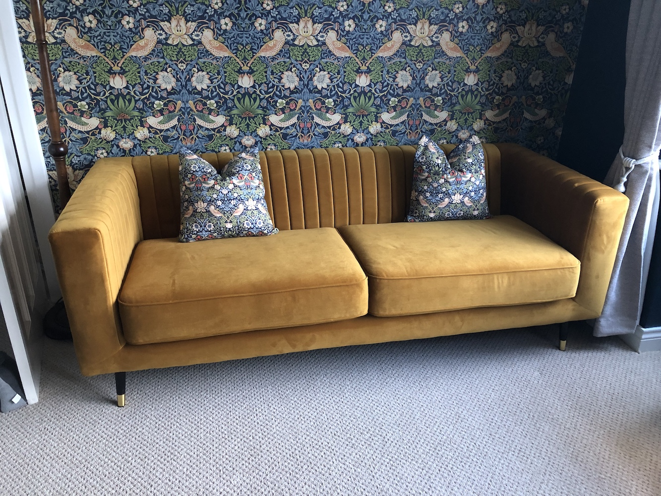 Slender mustard sofa with stitching on the backrest